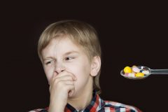 Young Boy with hand Over Mouth Refusing Pills