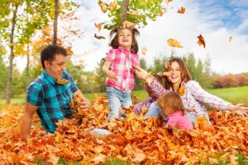 Mum and girls throw leaves up in the air playing with kids in autumn park happy and smiling.