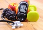 Glucose meter with medical stethoscope, fruits and dumbbells for using in fitness, concept of diabetes, healthy lifestyles and nutrition.