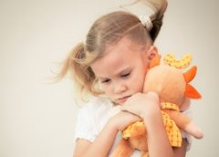 little girl cuddling orange soft toy