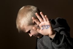 Boy with Stop Written on Hand