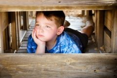 Boy in Blue Shirt Hiding and Looking Unhappy