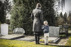 Woman and child looking at gravestone on graveyard.