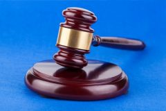 Wooden Brown Judges Gavel on Blue Table Background