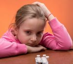 Little Girl Looking Upset Pills on Table