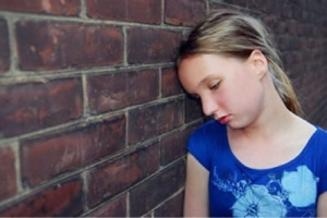Girl leaning on a wall.