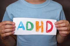 Young boy holds ADHD text written on sheet of paper.