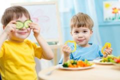 Kids eating healthy food in kindergarten or at home.