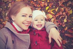 Happy mum and daughter outside in autumn.