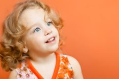 Small girl with blonde, curly hair smiling.