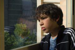 A sad boy looking out through a window.