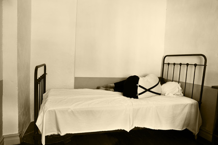 Depressed man on bed in a mental hospital.