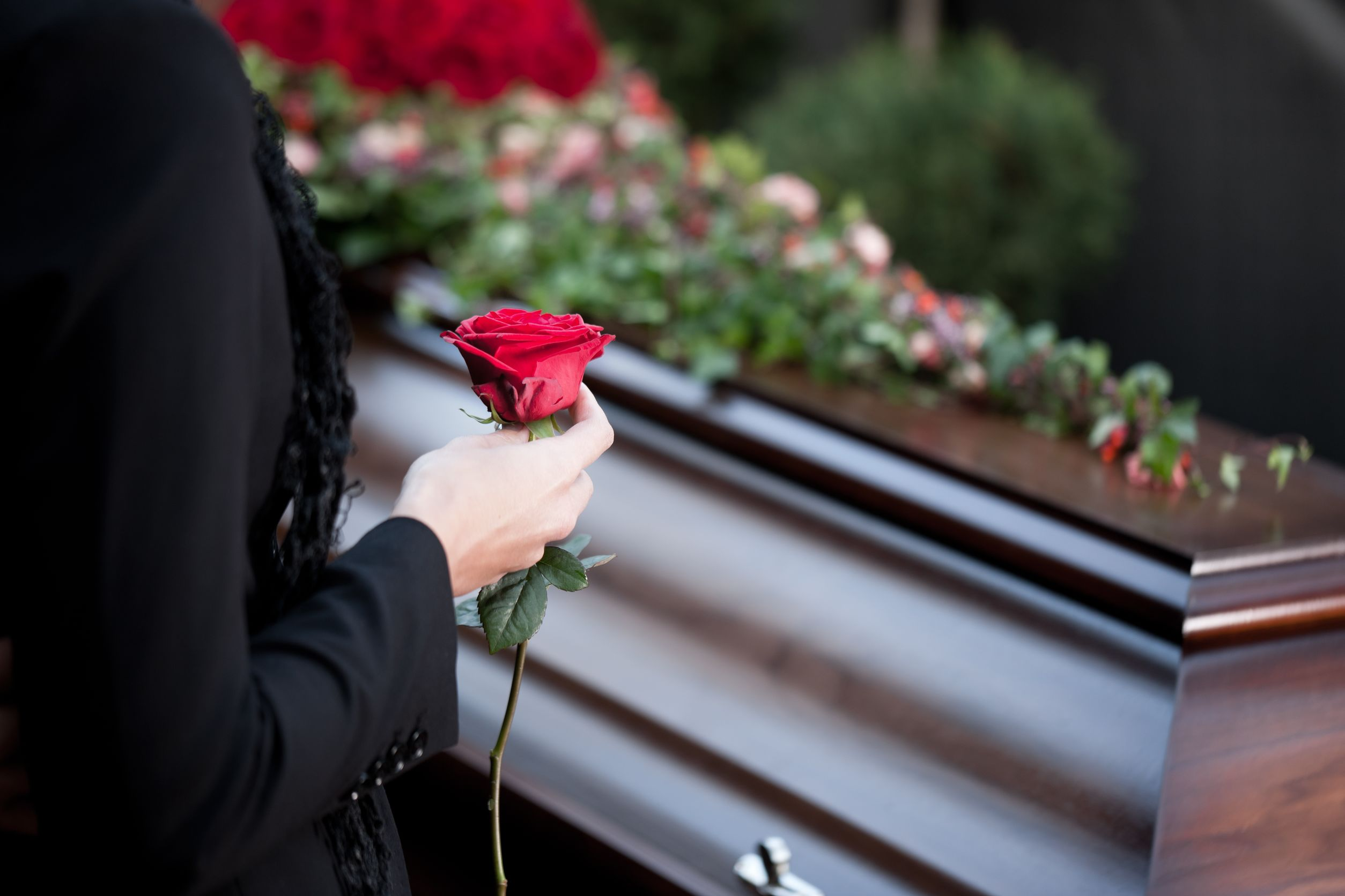 Woman with a rose near a coffin.