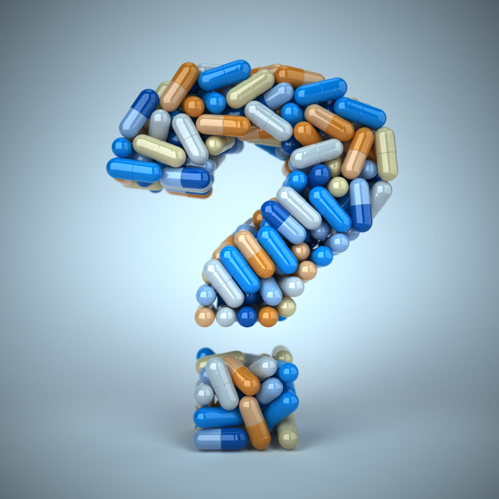 Pills or capsules as a question mark on a blue background.